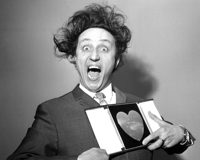 FILE - In this March 8, 1966 file photo, comedian Ken Dodd poses with his award for Show Business Personality of the Year, presented to him at the Variety Club's luncheon at the Savoy Hotel, London. British comedian Ken Dodd, whose seven-decade career stretched from the music-hall era to the age of social media, has died. He was 90. Publicist Robert Holmes says Dodd died Sunday, March 11, 2018 at his Liverpool home, the same house where he was born in 1927. (PA via AP, File)