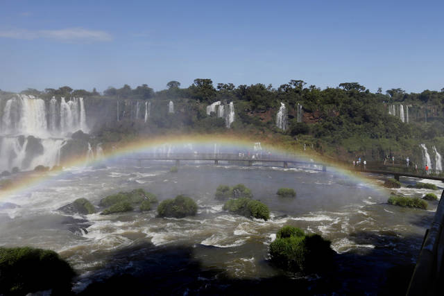 FILE - This March 15, 2015 file photo shows a rainbow at Iguazu Falls from the Brazilian side in Foz do Iguazu, Brazil. On Friday, March 16, 2018, The Associated Press has found that stories circulating on the internet that Coca-Cola and Nestle are negotiating for rights to the Guarani aquifer system, a massive fresh water reserve in South America, are untrue. Iguazu Falls is located on Brazil's border with Argentina. (AP Photo/Jorge Saenz, File)