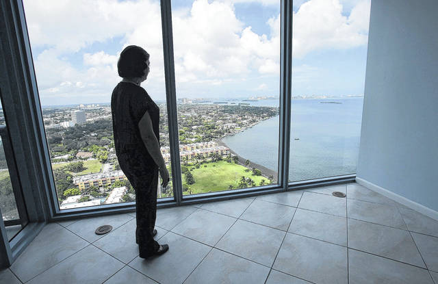 A prospective buyer looks at the view from The Blue condominium in Miami in 2010. A house with a fabulous view can be hard for a homebuyer to resist. But seeing the mountains, water or city lights from the comfort of home comes at a price.