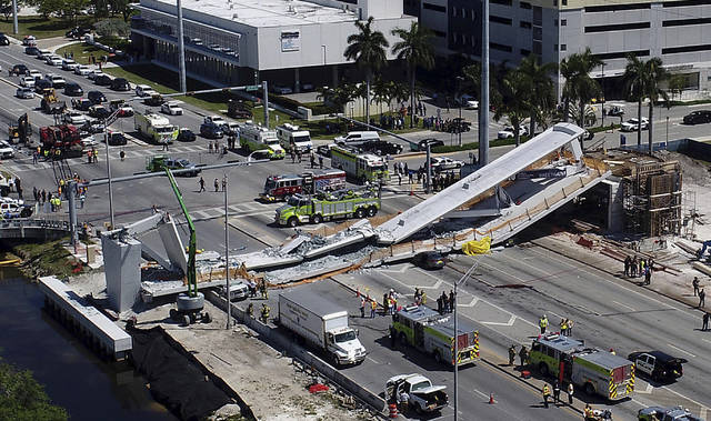 FILE - In this Thursday, March 15, 2018 file photo, emergency personnel respond after a pedestrian bridge collapsed onto a highway at Florida International University in Miami. On Friday, March 23, 2018, The Associated Press has found that stories circulating on the internet that a female-led construction company was responsible for deadly bridge collapse, are untrue. (Pedro Portal/Miami Herald via AP)