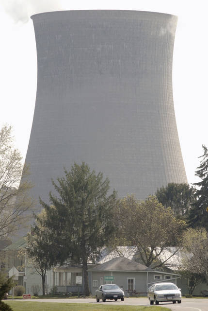 FILE- This 2002 file photo shows a tower for American Electric Power's Gen. James M. Gavin plant looming over Cheshire, Ohio. Utility companies around the nation are reacting in varied ways to states' demands that they return proceeds of the federal tax cut to their customers. Some companies are readily complying, while others are balking.