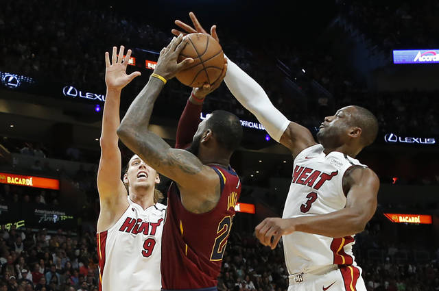 Miami Heat guard Dwyane Wade (3) blocks a shot by Cleveland Cavaliers forward LeBron James (23) in the first quarter during an NBA basketball game, Tuesday, March 27, 2018, in Miami. At left is Heat forward Kelly Olynyk (9). (AP Photo/Joe Skipper)