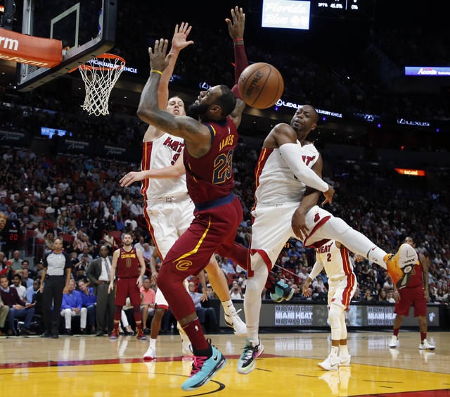 Miami Heat guard Dwyane Wade, right, blocks a shot by Cleveland Cavaliers forward LeBron James (23) in the first quarter during an NBA basketball game, Tuesday, March 27, 2018, in Miami. At left is Heat forward Kelly Olynyk (9). (AP Photo/Joe Skipper)