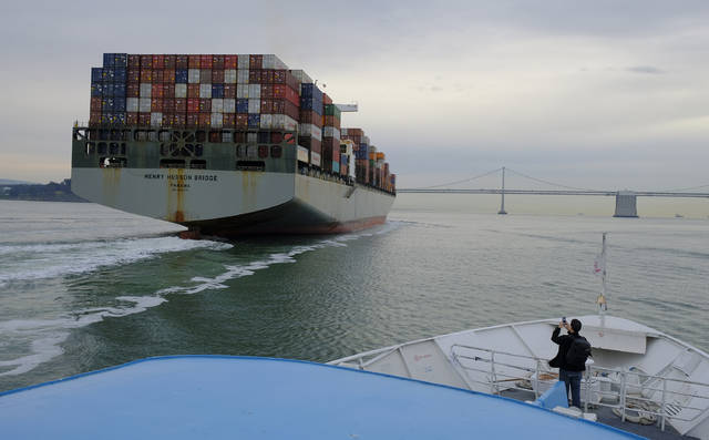 FILE- In this March 7, 2018, file photo, a man standing on the bow of a Golden Gate Ferry takes a picture of a container ship as it heads toward the San Francisco-Oakland Bay Bridge in San Francisco. On Wednesday, March 28, the Commerce Department issues its final estimate of how the U.S. economy performed in the October-December quarter. (AP Photo/Eric Risberg, File)