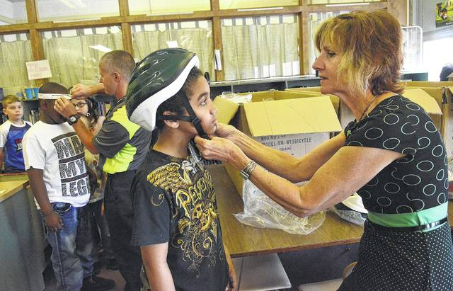 Physicians coordinator, Cindy Garmatter of Lima Memorial Health System, helps George Bryant, 9, a third-grader at Perry Elementary School get fitted for a bicycle helmet on Thursday. Thanks to a grant from the Ohio Chapter of the American Academy of Pediatrics in Collaboration with Sam's Club approximately 130 children's bike helmets were provided to the health systems for distribution at area schools. Craig J. Orosz | The Lima News