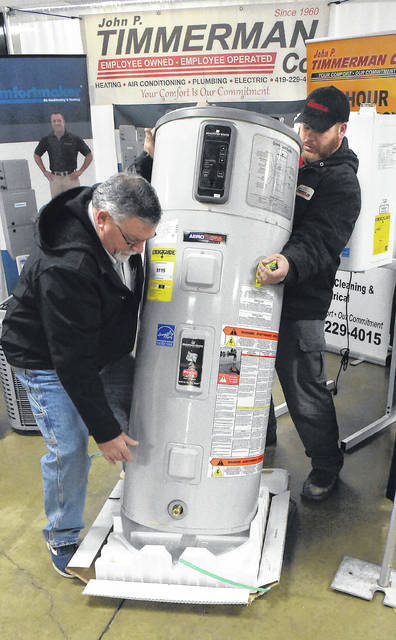 Mike Theobald, left, and Travis Haskins, employees for John P. Timmerman heating and air conditioning in Elida, build a display at the Lima Noon Optimist Home and Garden Show at the Allen County Fairgrounds this weekend.