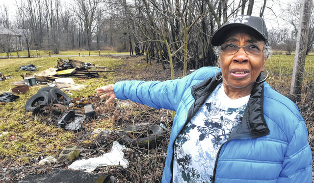 Mary Williamson points to garbage dumped in a vacant lot next to her home on East 12th Street in Lima.