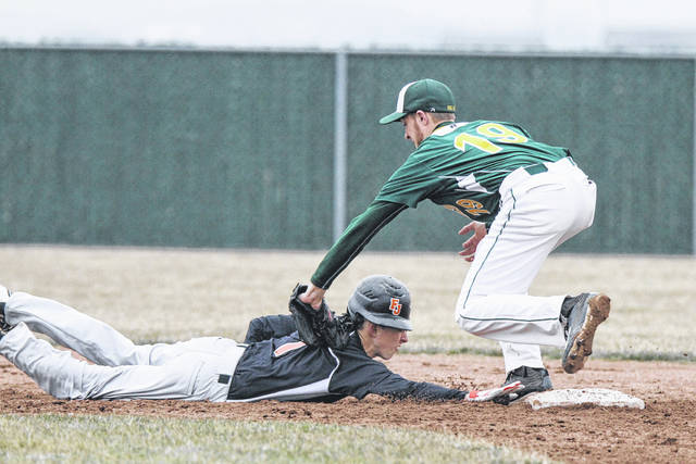 Ottoville's Clayton Schnipke completes the pick-off of Fort Jennings' Simon Smith as he tries to steal third base on Wednesday evening at Ottoville.