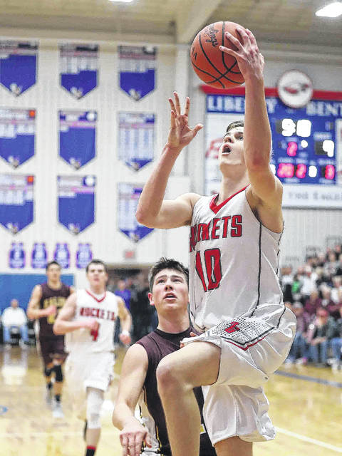 Pandora-Gilboa's Drew Johnson goes up for a basket against Kalida's Owen Recker during Friday night's Division IV district final at Liberty-Benton High School.