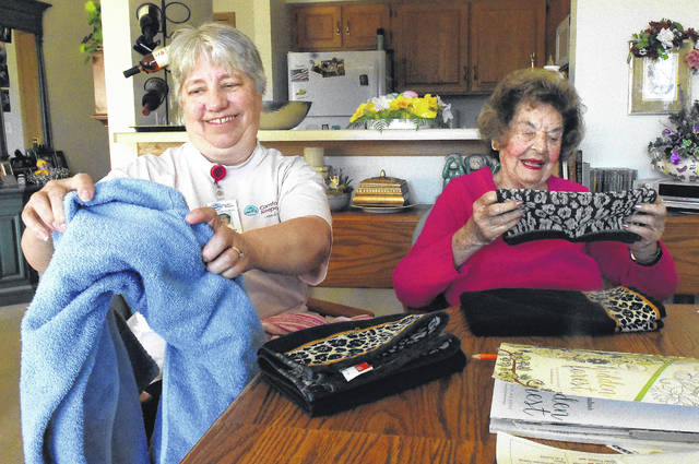 Judy Landwehr, left, of Comfort Keepers, folds towels with Patricia Cheney, 90, a resident at Primrose Retirement Community of Lima.