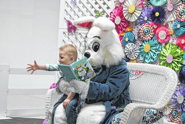 Cooper Garver, 2 1/2, reaches out to his mother as he sits on the lap of the Easter Bunny. The Lima Mall offered a chance for special needs families to come out and visit in a less hectic, less noisy environment Sunday morning.