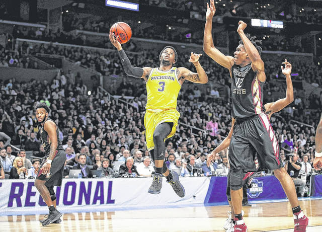 Xavier Simpson (3), of Michigan, drives to the basket during the Wolverines' 58-54 win over Florida State in the West Regional championship game in Los Angeles on Saturday night.