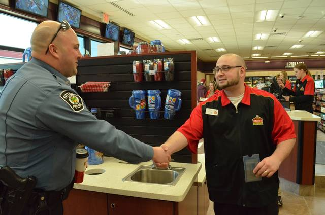 "Ottawa Police Officer Shane Vance introduces himself to Casey's store manager Dann Wiler while the officer the variety of new coffee options during the soft opening of the new convenience store Friday. ""Variety is a good thing, especially for cops,"" Vance said while looking at the different coffee flavors."