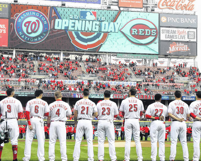 Reds players stand during Opening Day pregame ceremonies Friday before facing Washington at Great American Ball Park in Cincinnati.