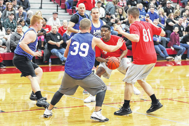 Jordan Pughsley, of the Lima Fire Department, takes a shot against the Lima Police Department in the Make A Wish benefit basketball game held at Lima Senior High School on Friday evening.