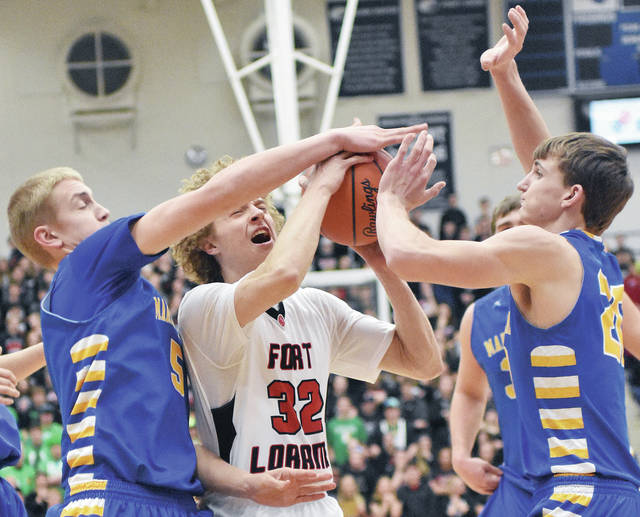 Marion Local's Nathan Bruns, left, and Nick Tangeman defend Fort Loramie's Dillon Braun during Friday night's Division IV regional championship at Trent Arena in Kettering.