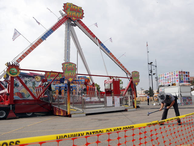 FILE - In this July 27, 2017 file photo, an Ohio State Highway Patrol trooper removes a ground spike in front of the Fire Ball ride at the Ohio State Fair, in Columbus, Ohio. Attorneys for the family of a teenager killed in a thrill ride accident at the Ohio State Fair and others left with life-changing injuries believe the state's inspectors missed obvious warning signs. But the attorneys won't include the state in any lawsuits or financial settlements because Ohio, like many other states, gives its carnival ride inspectors immunity from accusations of negligence. (AP Photo/Jay LaPrete, File)