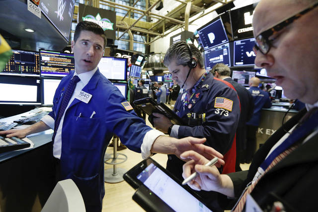 Specialist Thomas McArdle, left, works with traders John Panin, center, and Jeffrey Vazquez on the floor of the New York Stock Exchange, Monday, April 2, 2018. U.S. stocks are skidding Monday morning after China raised import duties on U.S. pork, apples and other products. (AP Photo/Richard Drew)