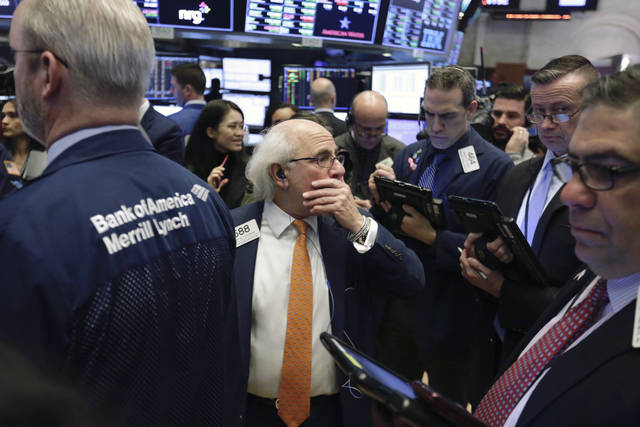 Trader Peter Tuchman, center, stands on the floor of the New York Stock Exchange while waiting for Spotify's IPO, Tuesday, April 3, 2018. The Swedish company will make its stock market debut Tuesday, casting a spotlight on its early lead in music streaming. (AP Photo/Richard Drew)
