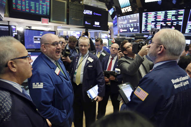 Specialist Peter Giacchi, left, calls out prices before Spotify's IPO on the floor of the New York Stock Exchange, Tuesday, April 3, 2018. The Swedish company will make its stock market debut Tuesday, casting a spotlight on its early lead in music streaming. (AP Photo/Richard Drew)
