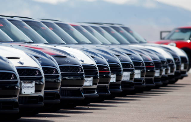 In this Friday, March 30, 2018, photograph, a line of unsold 2018 Cooper Clubmen sit in a long row at a Mini dealership in Highlands Ranch, Colo. U.S. auto sales grew 6.3 percent in March on rising sales of SUVs and pickup trucks. (AP Photo/David Zalubowski)