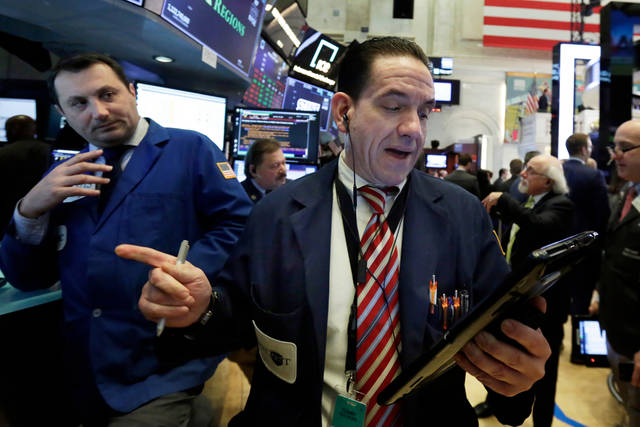 Trader Tommy Kalikas, right, works on the floor of the New York Stock Exchange, Monday, April 9, 2018. Stocks are opening solidly higher on Wall Street, led by gains in big technology companies. (AP Photo/Richard Drew)