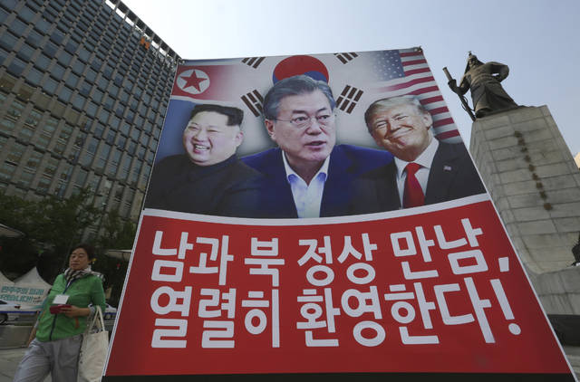 """A banner showing U.S. President Donald Trump, right, South Korean President Moon Jae-in and North Korean leader Kim Jong Un, left, is displayed to support the summit between two Koreas in Seoul, South Korea, Friday, April 27, 2018. The sign reads """" We welcome the summit between South and North Korea."""" (AP Photo/Ahn Young-joon)"""