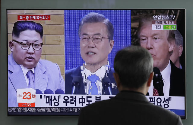 In this March 27, 2018 photo, a man watches a TV screen showing file footages of U.S. President Donald Trump, right, South Korean President Moon Jae-in, center, and North Korean leader Kim Jong Un, left, during a news program at the Seoul Railway Station in Seoul, South Korea. The stakes will be high when North Korean leader Kim Jong Un and South Korean President Moon Jae-in sit down Friday, April 27, 2018 in the no man's land that forms the world's most heavily armed border. (AP Photo/Lee Jin-man)