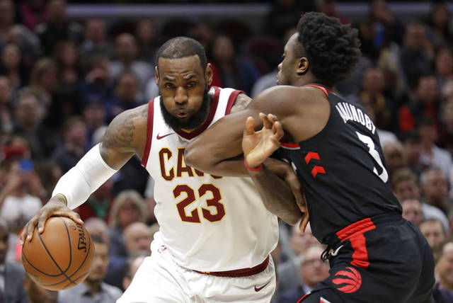 The Cavaliers' LeBron James, left, drives against Toronto's OG Anunoby during Tuesday night's game in Cleveland.