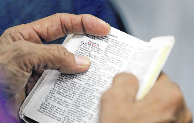 FILE- In this Sept. 3, 2017, file photo, a man holds a bible during service at Christ United Church in the aftermath of Hurricane Harvey in Cypress, Texas. Bible sales would not be banned in California under proposed state legislation, contrary to widely shared claims by multiple online sites.