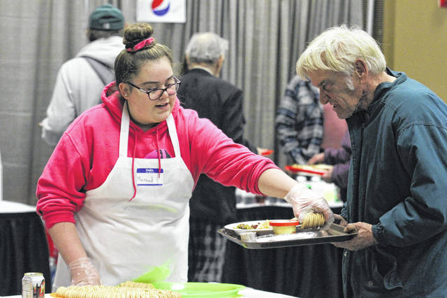 Mairead Farler (left), 13 of Bath, takes time on Sunday to help give out food to families at the Tom Ahl Easter dinner held at the Lima Civic Center.