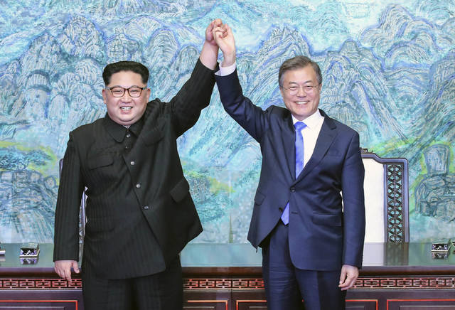 "File-This April 27, 2018, file photo shows North Korean leader Kim Jong Un, left, and South Korean President Moon Jae-in raising their hands after signing a joint statement at the border village of Panmunjom in the Demilitarized Zone, South Korea. North Korea readjusted its time zone to match South Korea's on Saturday and described the change as an early step toward making the longtime rivals ""become one"" following a landmark summit. North Korean leader Kim Jong Un promised to sync his country's time zone with the South's during his April 27 talks with South Korean President Moon Jae-in. A dispatch from the North's Korean Central News Agency says that promise was fulfilled Saturday by a decree of the nation's Presidium of the Supreme People's Assembly. (Korea Summit Press Pool via AP, File)"
