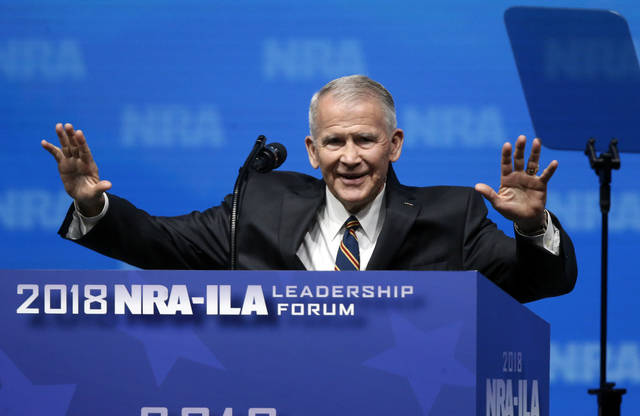 In this May 4, former U.S. Marine Lt. Col. Oliver North acknowledges attendees as he gives the Invocation at the National Rifle Association-Institute for Legislative Action Leadership Forum in Dallas. The NRA announced Monday that North will become president of the National Rifle Association of America within a few weeks.