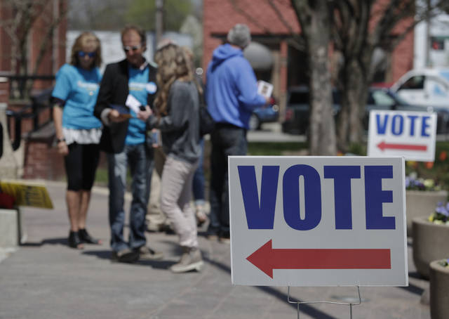 In this Friday, April 27, 2018 photo, electioneers greet voters outside the Hamilton County Government Center during early voting in Noblesville, Ind. The U.S. Department of Homeland Security is facing a backlog of requests for comprehensive cybersecurity reviews of state election systems. Among those still waiting is Indiana, which is one of four states with primaries on Tuesday, May 8, 2018. (AP Photo/Michael Conroy)
