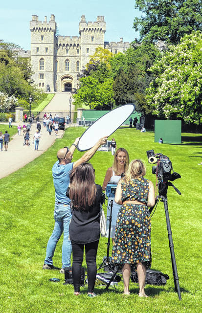 British TV presenter Amanda Holden, center of group, reacts during filming for the US television show Inside Edition, on the Long Walk in Windsor, England, on Monday ahead of Saturday's wedding of Britain's Prince Harry and Meghan Markle. Worldwide media outlets begin setting up for their coverage of the marriage upcoming weekend, reporting from the town of Windsor.