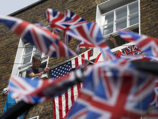 People attach a U.S. flag when decorating their home along the route the royal couple will travel in Windsor, England, on Friday. Preparations continue in Windsor ahead of the royal wedding of Britain's Prince Harry and Meghan Markle on Saturday.