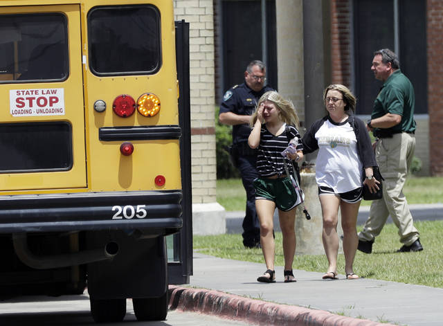 A student, left, reacts after retrieving her belongings inside Santa Fe High School in Santa Fe, Texas, on Saturday, May 19, 2018. Students and teachers were allowed to return to parts of the school to gather their belongings. A gunman opened fire inside the school Friday, May 18  killing several people. (AP Photo/David J. Phillip)
