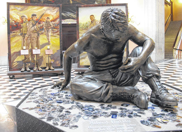 "This Monday, May 21, 2018, photo shows a memorial paying tribute to a central Ohio-based Marine reserve company that lost 22 Marines and a Navy Corpsman in Iraq in 2005, including a newly unveiled bronze statute, ""Silent Battle,"" drawing attention to suicides among veterans, is displayed at the Ohio Statehouse in Columbus, Ohio."