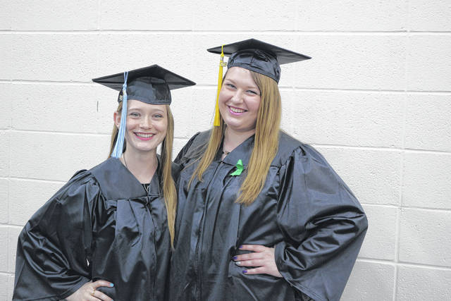 Ashley Backs (left) and Emma Eickholt pose prior to Bluffton's commencement Sunday.