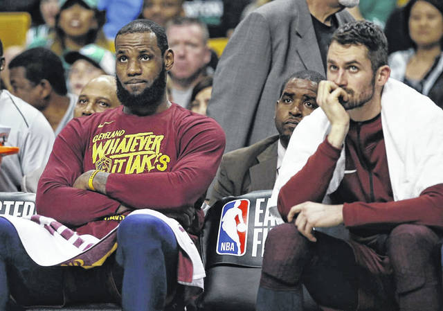 LeBron James, left, and center Kevin Love, right, watch from the bench during the fourth quarter of Game 1 of the NBA basketball Eastern Conference Finals against the Boston Celtics on Sunday. Boston won 108-83.