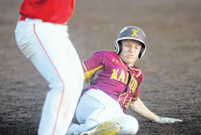 Kalida's Matt Kehres safely slides into third base during a Wednesday Division IV district semifinal against Patrick Henry at Defiance High School.