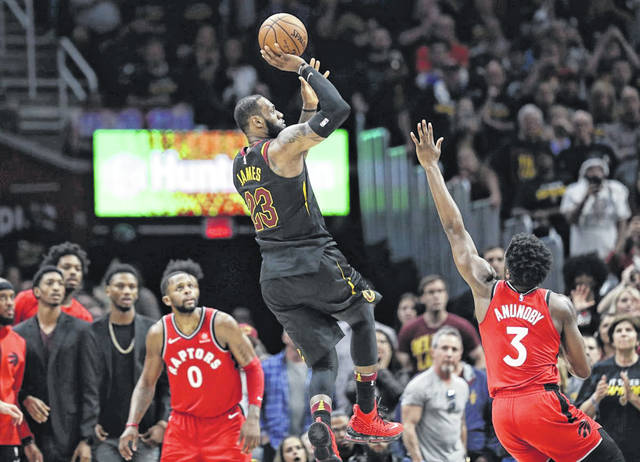 LeBron James (23), of the Cleveland Cavaliers, hits the game-winning shot as Toronto Raptors' OG Anunoby (3) and CJ Miles (0) watch at the end of the Cavaliers' 105-103 win over the Raptors on Saturday night.