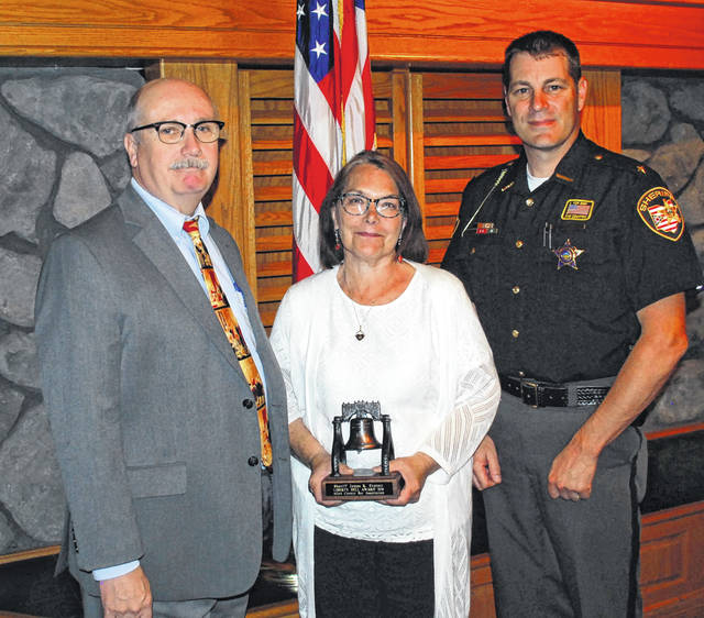 Pam Everett, the widow of longtime Allen County Sheriff's Office employee James Everett, on Friday accepted the Allen County Bar Association's Liberty Bell Award on behalf of her late husband. Presenting the award was Lima Law Director Tony Geiger. At right is Sheriff Matt Treglia.
