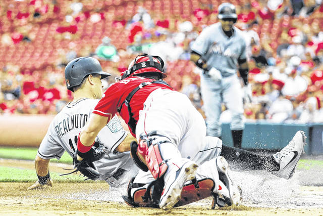 Miami Marlins runner J.T. Realmuto, left, beats the throw to Cincinnati Reds catcher Tucker Barnhart to score on an RBI sacrifice fly by Starlin Castro off starting pitcher Brandon Finnegan in the second inning of the Marlins' 8-5 win over the Reds on Sunday in Cincinnati.