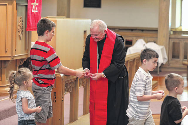 Rev. David Harris interacts with children during his last service as pastor at the Trinity United Methodist Church on Sunday morning.