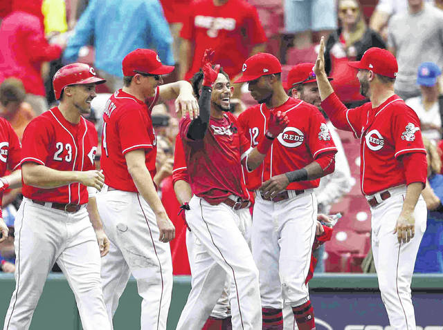 Cincinnati Reds' Billy Hamilton, center, celebrates the team's 5-4 win over the Chicago Cubs in 11 innings in the first baseball game of a doubleheader, Saturday, May 19, 2018, in Cincinnati. The Reds won 5-4. (AP Photo/Gary Landers)