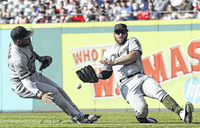 Chicago White Sox's Daniel Palka, right, cannot catch a ball hit by Cleveland Indians' Edwin Encarnacion in the fifth inning of a baseball game, Monday, May 28, 2018, in Cleveland. Yoan Moncada, left, watches. Encanacion was safe at second base for a double. (AP Photo/Tony Dejak)
