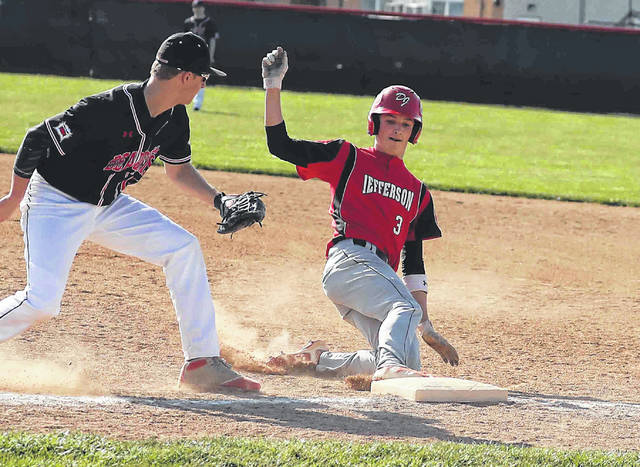 Jefferson's Hunter Haehn gets back to first base safely as Spencerville's Hunter Stephen spins to make a tag at Spencerville High School Monday.