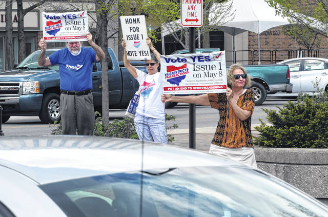 Jim Bode, left, Beth Sutton-Ramspeck and Teresa Heath hold signs for a honk and wave for Issue 1 in downtown Lima on Friday.