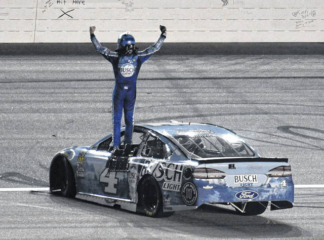 Kevin Harvick stands on his car as he celebrates his win in the NASCAR Cup Series KC Masterpiece 400 auto race at Kansas Speedway on Saturday night in Kansas City, Kan.